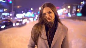 Ritratto di bella giovane donna alla notte nella città Ragazza attraente del movimento lento che guarda alla macchina fotografica stock footage