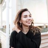 Ritratto di bella giovane donna allegra con un sorriso attraente in un cappotto nero alla moda vicino ad un caffè aperto di estat fotografia stock