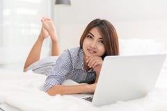 Ritratto di bella giovane donna asiatica felice che lavora al letto immagini stock