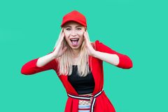 Ritratto di bella giovane donna bionda stupita dei pantaloni a vita bassa in blusa e cappuccio rossi, stando, toccando il suo fro fotografia stock