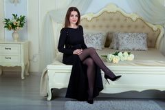 Ritratto di bella giovane donna castana che si siede nella camera da letto fotografia stock
