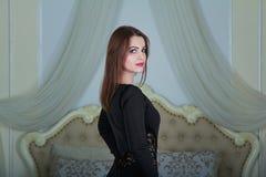 Ritratto di bella giovane donna castana che sta nella camera da letto immagini stock