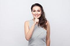 Ritratto di bella giovane donna castana felice divertente con trucco e la condizione a strisce del vestito, sorridente ed esamina immagine stock