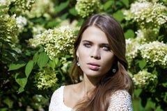 Ritratto di bella giovane donna castana nel fiore di primavera Immagini Stock Libere da Diritti