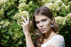 Ritratto di bella giovane donna castana nel fiore di primavera Immagine Stock