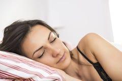 Ritratto di bella giovane donna che dorme nel letto bianco Immagine Stock