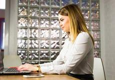 Ritratto di bella giovane donna che lavora con il computer portatile nel suo ufficio Immagini Stock