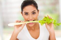 Donna che mangia sedano Fotografie Stock Libere da Diritti