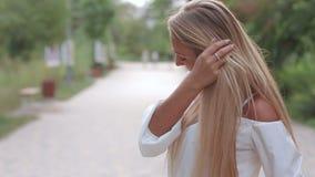 Ritratto di bella giovane donna con capelli lunghi sopra il fondo del parco, trucco naturale d'uso video d archivio