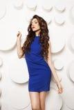 Ritratto di bella giovane donna con capelli marroni lunghi ricci in vestito blu Immagine Stock