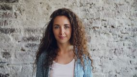 Ritratto di bella giovane donna con capelli ricci lunghi che stanno contro il muro di mattoni, sorridenti ed esaminanti macchina  stock footage