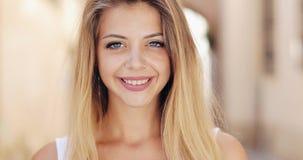 Ritratto di bella giovane donna con con gli occhi azzurri ed il sorriso attraente stock footage