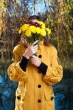 Ritratto di bella giovane donna con i fiori davanti lei fotografia stock