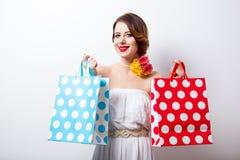 Ritratto di bella giovane donna con i sacchetti della spesa punteggiati sulla t Immagini Stock Libere da Diritti