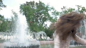 Ritratto di bella giovane donna con il sorriso attraente Gode della vita e balla vicino alla fontana video d archivio