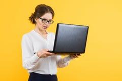 Ritratto di bella giovane donna imbarazzata sicura di affari che lavora al computer portatile su fondo giallo Immagine Stock