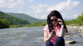 Ritratto di bella giovane donna sorridente con i vetri e lo smartphone rotondi Fondo del fiume della montagna carpatica Fotografia Stock Libera da Diritti