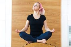 Ritratto di bella giovane donna sportiva con capelli rosa che si siedono Lotus Pose Meditation Relaxation sul backbend b di Vipar immagini stock libere da diritti