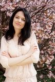 Ritratto di bella giovane donna su un fondo dei fiori di ciliegia rosa in primavera, fotografia stock libera da diritti