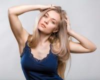 Ritratto di bella giovane donna su un fondo grigio fotografie stock libere da diritti