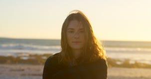 Ritratto di bella giovane donna sulla spiaggia durante il tramonto 4k video d archivio