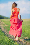 Ritratto di bella giovane donna in un vestito rosso su un fondo del cielo e dell'erba di estate Fotografia Stock Libera da Diritti