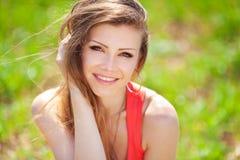Ritratto di bella giovane donna in un vestito rosso su un fondo del cielo e dell'erba di estate Immagini Stock Libere da Diritti