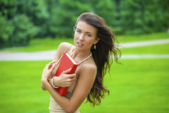 Ritratto di bella giovane ragazza castana con il libro rosso sul BAC Fotografie Stock Libere da Diritti