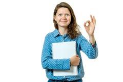 Ritratto di bella giovane ragazza dello studente che mostra segno giusto Fotografia Stock