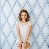 Ritratto di bella giovane ragazza dolce con un sorriso affascinante ed i corni sulla testa di una giraffa che posa e che sorride Fotografia Stock
