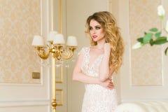 Ritratto di bella giovane sposa Una ragazza sta posando in una camera di albergo La signora sta filando in suo vestito da sposa Immagine Stock