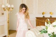 Ritratto di bella giovane sposa Una ragazza sta posando in una camera di albergo La signora sta filando in suo vestito da sposa Immagini Stock