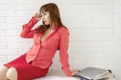 Ritratto di bella ragazza di affari del receptionist che si siede allo scrittorio su un fondo bianco fotografie stock libere da diritti