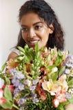 Ritratto di bella ragazza africana che sorride esaminando il mazzo della tenuta della macchina fotografica dei alstroemerias Fotografia Stock Libera da Diritti