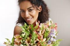 Ritratto di bella ragazza africana che sorride esaminando il mazzo della tenuta della macchina fotografica dei alstroemerias Immagine Stock