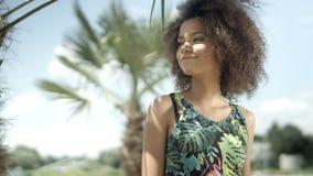 Ritratto di bella ragazza afroamericana adolescente sulla spiaggia tropicale che sorride ad una macchina fotografica video d archivio