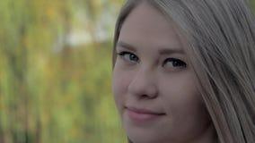 Ritratto di bella ragazza bionda con capelli d'ondeggiamento che esaminano macchina fotografica nel parco il giorno soleggiato stock footage