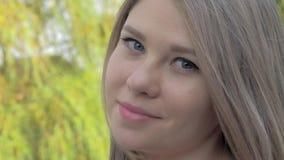 Ritratto di bella ragazza bionda con capelli d'ondeggiamento che esaminano macchina fotografica nel parco il giorno soleggiato video d archivio