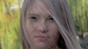 Ritratto di bella ragazza bionda con capelli d'ondeggiamento che esaminano macchina fotografica nel parco il giorno soleggiato archivi video