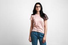 Ritratto di bella ragazza castana astuta in occhiali con trucco naturale, su fondo grigio Fotografia Stock Libera da Diritti