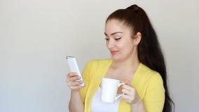Ritratto di bella ragazza castana che beve una bevanda calda da una tazza e tiene un telefono cellulare in sua mano giovane video d archivio