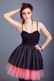 Ritratto di bella ragazza castana con i capelli di scarsità con gli orecchini rossi in un vestito nero fotografia stock libera da diritti