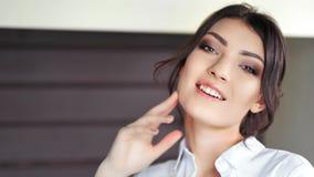 Ritratto di bella ragazza caucasica sexy con trucco perfetto che sorride e che esamina il primo piano della macchina fotografica archivi video