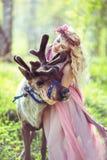 Ritratto di bella ragazza che abbraccia una renna Fotografie Stock