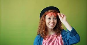 Ritratto di bella ragazza che alza gli occhiali da sole che sorridono sul fondo verde video d archivio