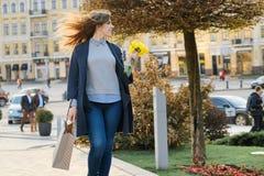 Ritratto di bella ragazza che cammina in citt?, giovane donna con il mazzo dei fiori gialli e sacchetto della spesa, citt? della  fotografie stock