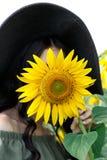 Ritratto di bella ragazza che copre il suo fronte di girasole Natura, vacanze estive, vacanza Donna con capelli lunghi in vestito immagine stock