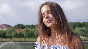 Ritratto di bella ragazza con capelli marroni che esaminano la macchina fotografica sui precedenti di un lago con una fontana stock footage