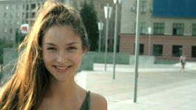 Ritratto di bella ragazza felice con capelli lunghi che stanno sulla via video d archivio