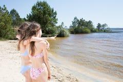 Ritratto di bella ragazza felice degli amici sul mare e di spruzzatura alla spiaggia Fotografia Stock